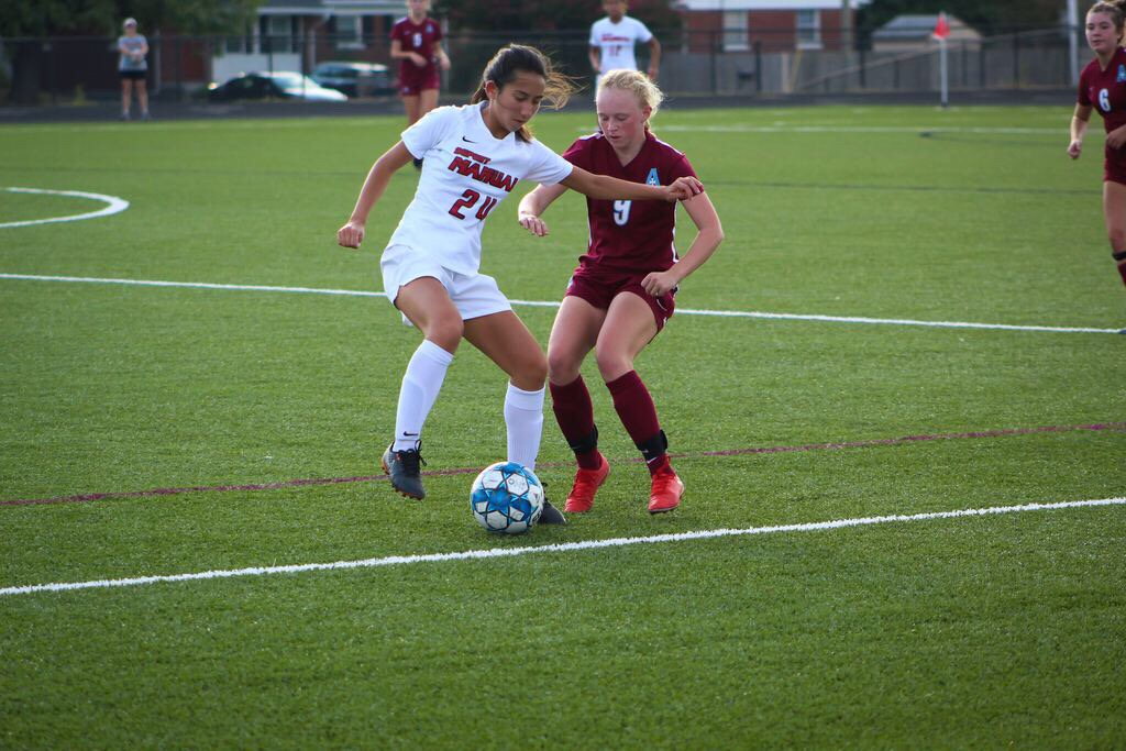 """""""Taylor Zekoski (10, MST) jostles with Assumption's Sarah Dahl in an attempt to prevent the ball from going out of bounds."""