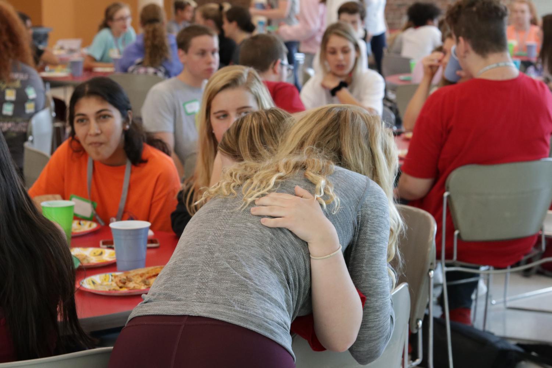Laila Marcum (11, HSU) hugs Isabella Robinson (9, ECE) before the meeting begins. Photo by Marilyn Buente.