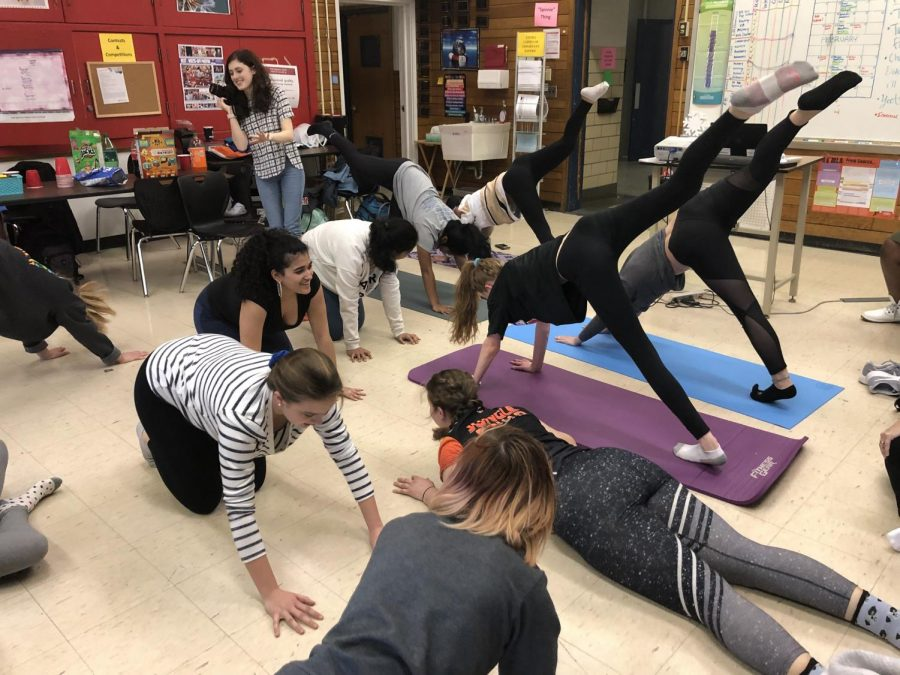 "Members of the 2018-19 Yoga Club show the yearbook staff a basic position during a break in the staff's worknight. ""We partnered with yearbook last year and we did one meeting with the yearbook. Ms. Mattingly said everyone is always really stressed,"" member Aanika Garre said. Photo by Pieper Mallett."