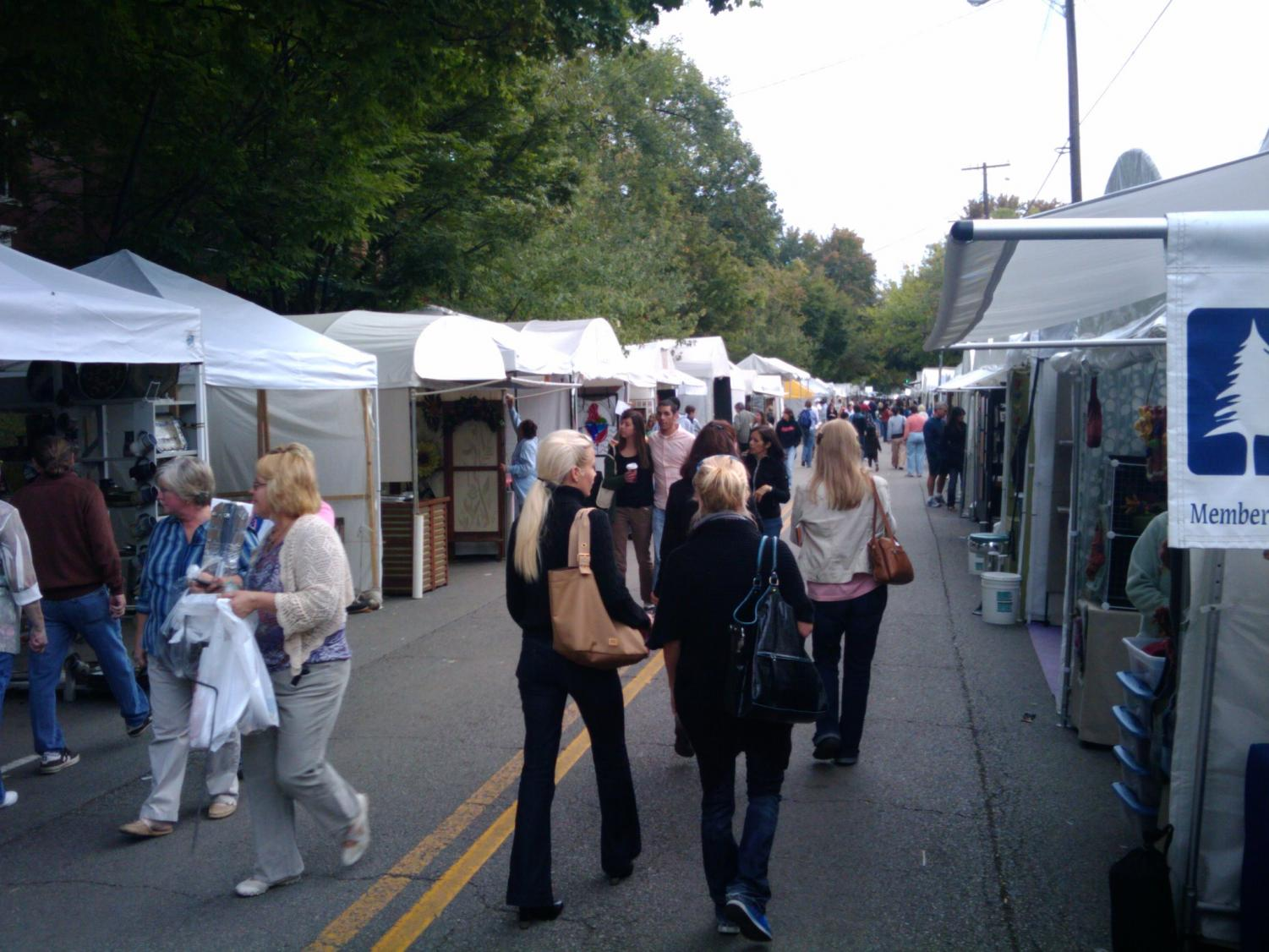 Visitors at the St. James Art Show peruse booths featuring with paintings, sculptures and other crafts.
