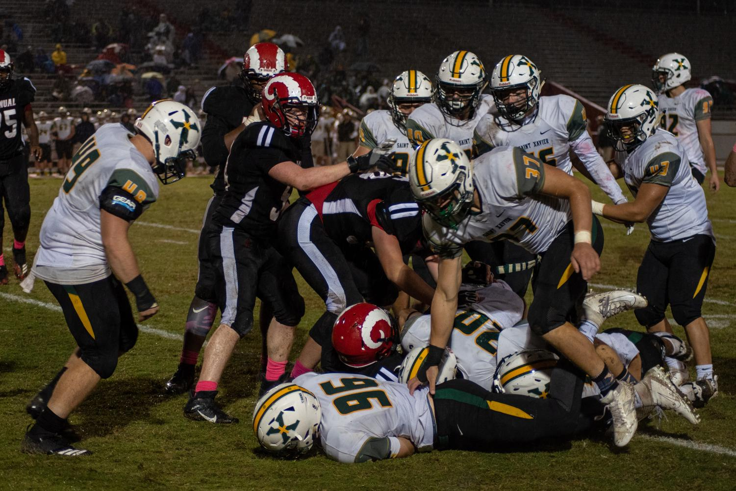 St. X's defense tackles Manual's running back. Photo by Cesca Campisano.
