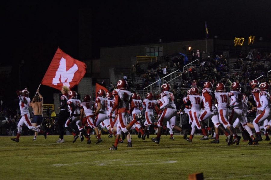 The Crimsons run out onto the field, led by student section leaders. Photo courtesy of Manual RedEye.