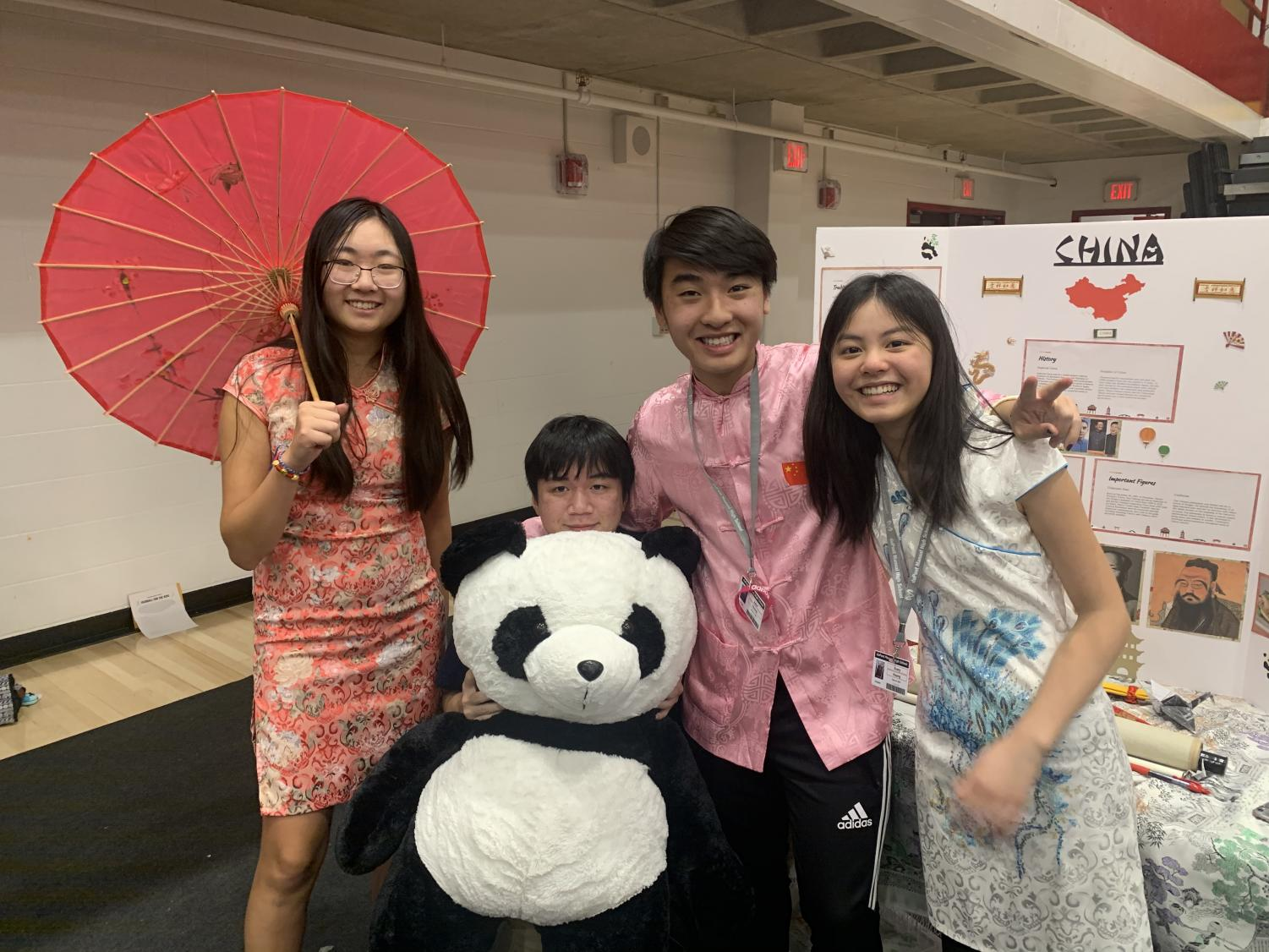 Students pose at the China booth at the multicultural fair. Photo by Macy Waddle