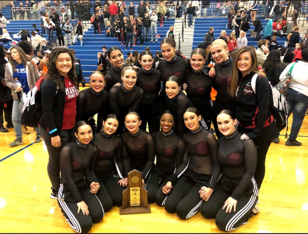 The Dazzler team sits together for a photo with the trophy. This trophy is for their win in the Small Hip Hop category. They placed in one out of two of their dances. Photo by Cassidy Adwell.