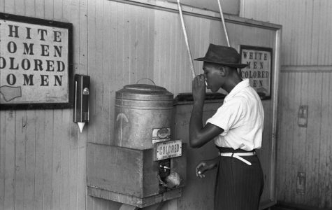 A man drinks at a water fountain that is separated from the white water fountain. Photo from  Library of Congress's Prints and Photographs division.