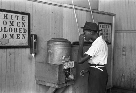 A man drinks at a water fountain that is separated from the white water fountain. Photo from  Library of Congress