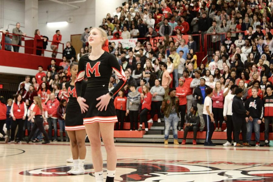 Cassidy Adwell (J&C, 10) looks to the crowd as the cheer squad begins their performance. Photo by Molly Gregory.