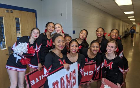 Manual's cheer team huddles together for a picture before going out on the mat. Photo by Abigail Sanders.