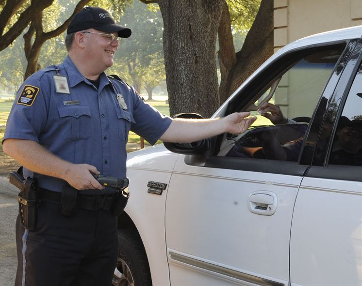 A security guard stops a vehicle. Manual will likely be required to have an armed security guard  both at Manual and YPAS.