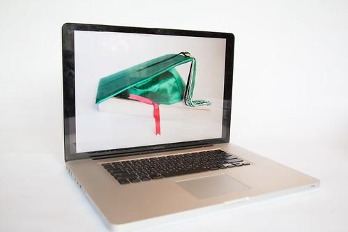 A grad cap on a screen to represent online graduation.