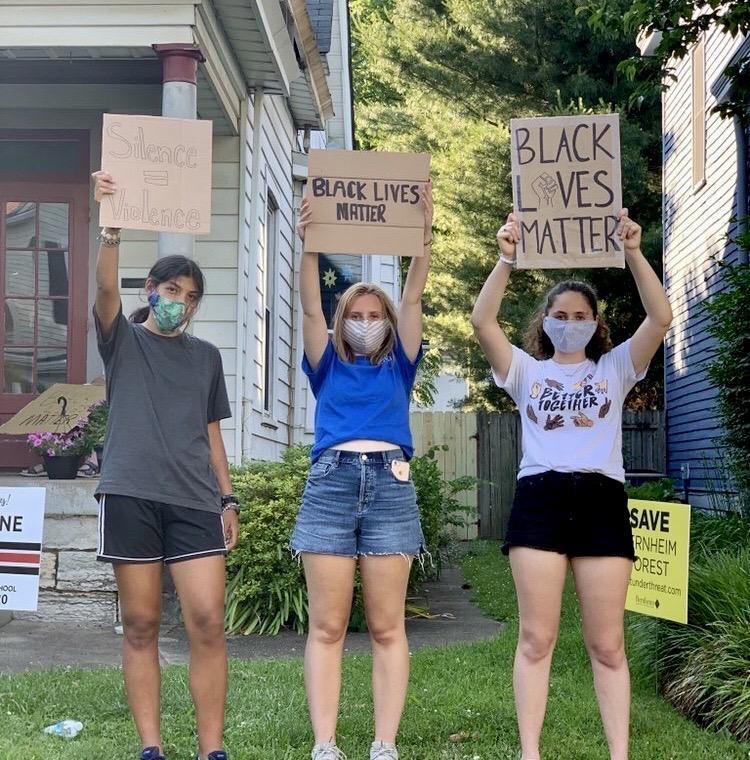 Adrienne Sato, a J&C graduate, Annie Garber, an SHA graduate, and Zayne Isom, a VA graduate, prepare for a protest. Photo by Candace Sawyer-Luijk.