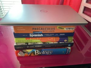 A laptop on top of school textbooks. Photo by Ofelia Mattingly.