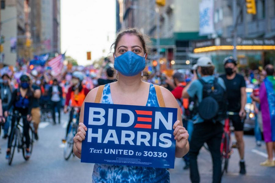 A woman proudly holding a sign as she celebrates Joe Biden's victory. Photo by Rom Matibag. Sourced from unsplash.com.