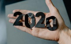 Someone holds crumpled paper cut into the numbers 2020. Photo by Kelly Sikkema. Sourced from unsplash.com.