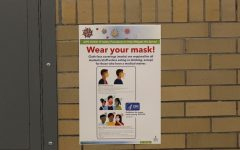 COVID-19 protocol posters hang in the hallways by bathrooms, encouraging people to wear their masks.