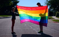 A parent and child holding a rainbow pride flag. Photo sourced from Unsplash. Taken by Sharon McCutcheon.