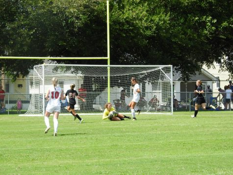 Manuals Kylie Seraphine (12, #1) launches to catch the ball blocking the St. Henry goal. Photo by Yaara Aleissa.