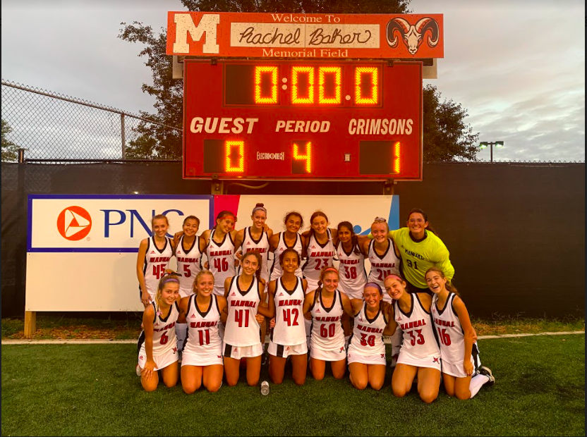 The JV Crimsons pose with the scoreboard after their win. Photo by Julia May.